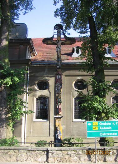 Das hölzernes Kreuz mit Skulpturen von Paweł Bryliński in Mikstat