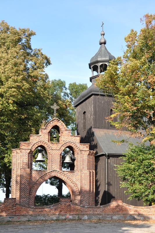 drewniany kościół z wieżą, murowana brama dzwonnica na trzy dzwony, drzewa, wczesna jesień