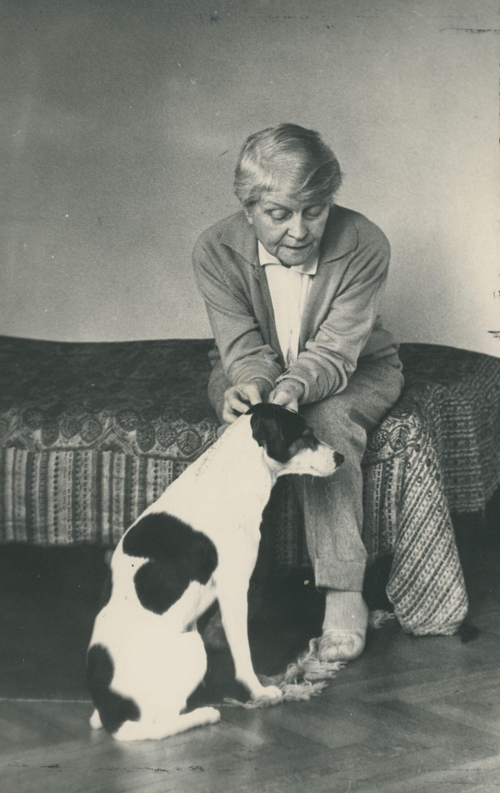Maria Dąbrowska siedzi na kanapie, obok pies
