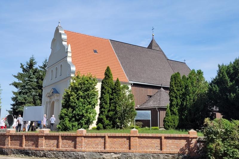 Kościół drewniano-murowany, część murowana z barokowym szczytem, kryta czerwoną dachówką. Całość otoczona ceglanym płotem