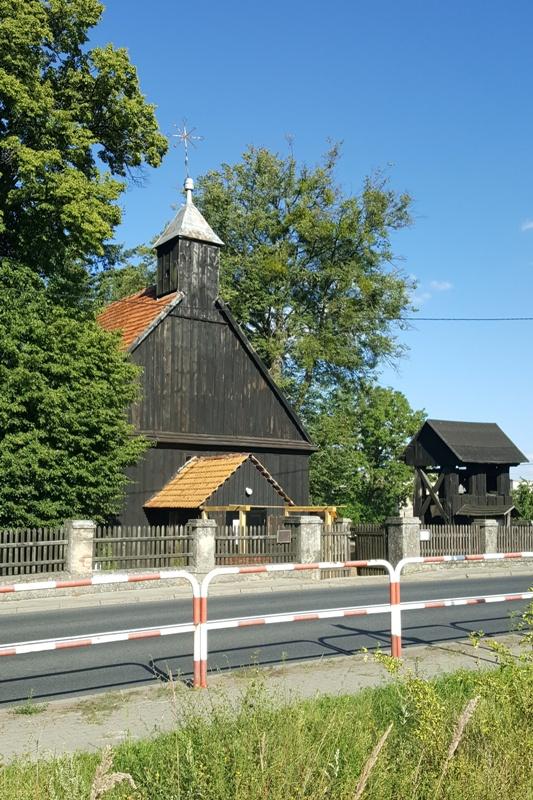 Kościół drewniany z wieżyczką sygnaturką, dach czerwony dwuspadowy, kuchta, obok drewniana dzwonnica