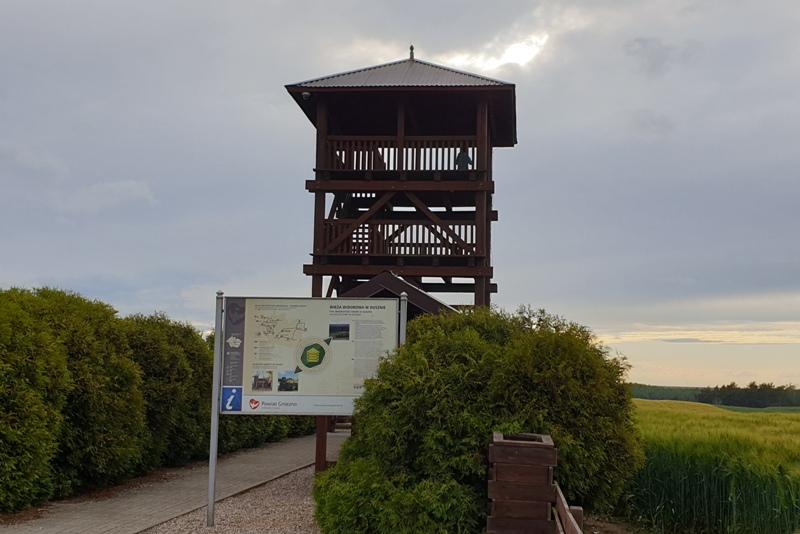 Punkt widokowy na wzniesieniu, drewniana konstrukcja, obok tablica informacyjna Szlaku Piastowskiego