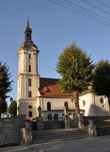 widok boczny na kościół, wysoka wieża, przycięte drzewa