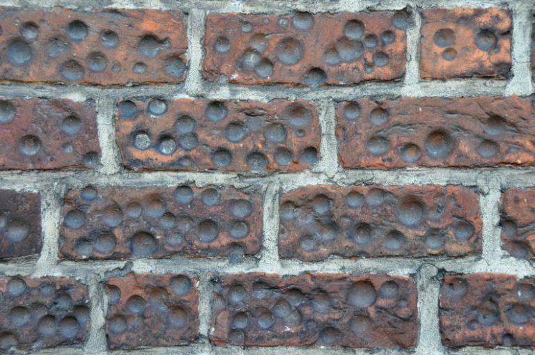Tajemnicze dołki w murze kościelnym w kościele w Pobiedziskach