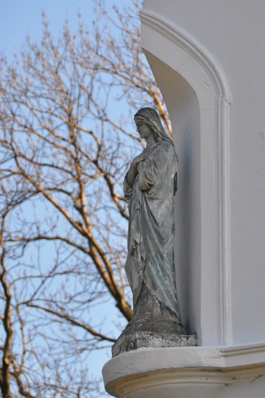 figura Maryi w niszy pałacu, na tle niebieskiego nieba