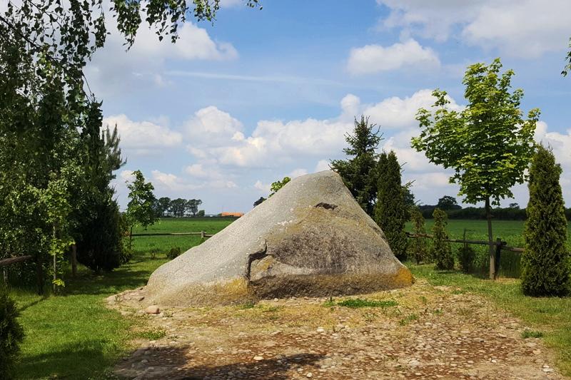 głaz narzutowy w kształcie trójkąta, wokół nasadzone drzewa