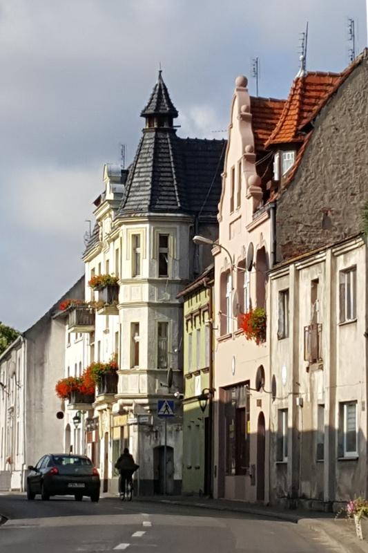 Widok na ulicę z dwupiętrowymi kamienicami, kwiaty w oknach