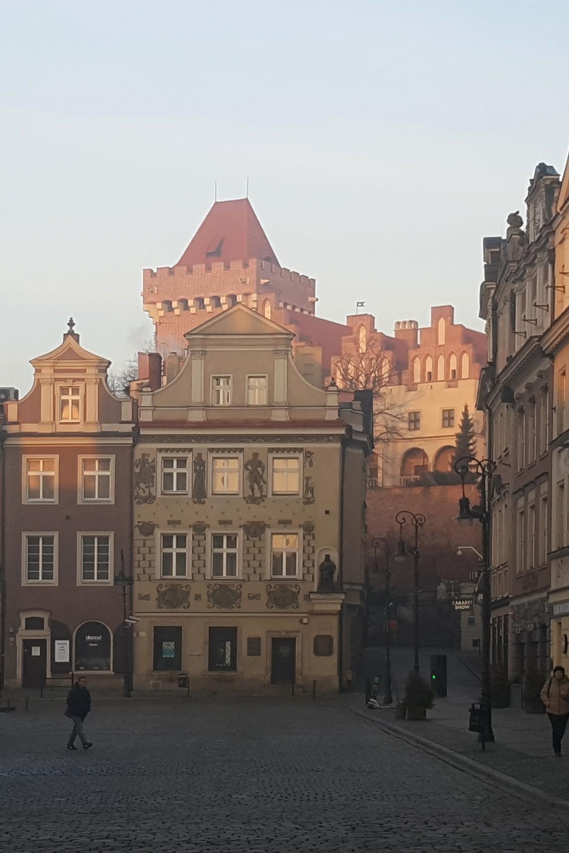 zabudowa zachodniej pierzei Starego Rynku w Poznaniu, kamieniczki z barokowymi szczytami, w tle wieża zamku królewskiego