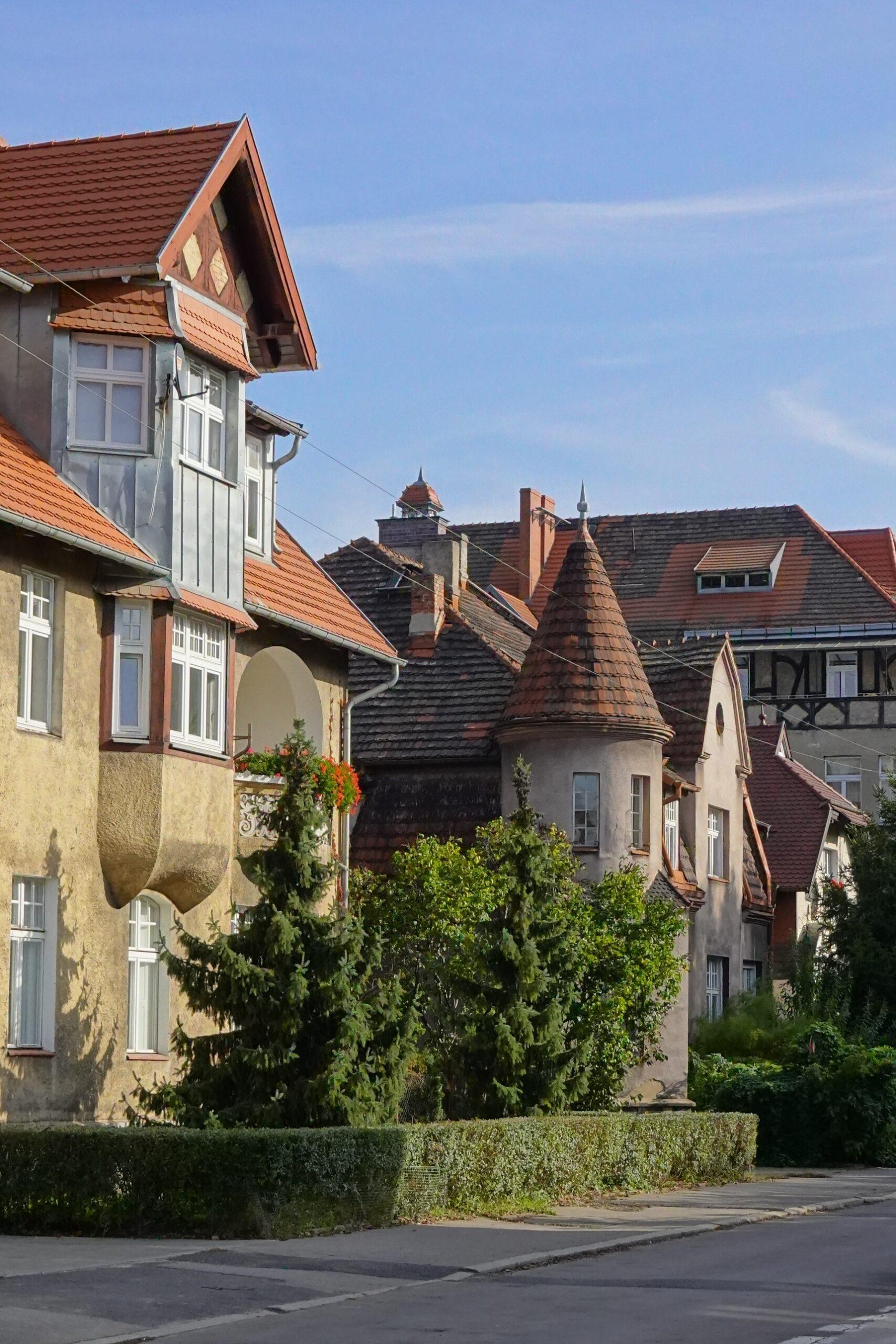 secesyjne wille wzdłuż ulicy, fantazyjne kształty, czerwone dachy, zieleń ogrodów