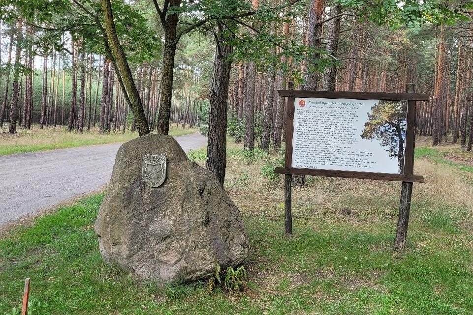 głaz na skraju leśnej drogi z herbem wsi. Obok tablica informacyjna z treścią legendy