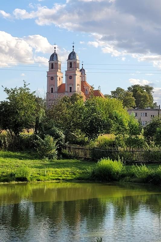 barokowy kościół, dwie wieże z kopułami w fasadzie, widok znad stawu, w otoczeniu zieleni