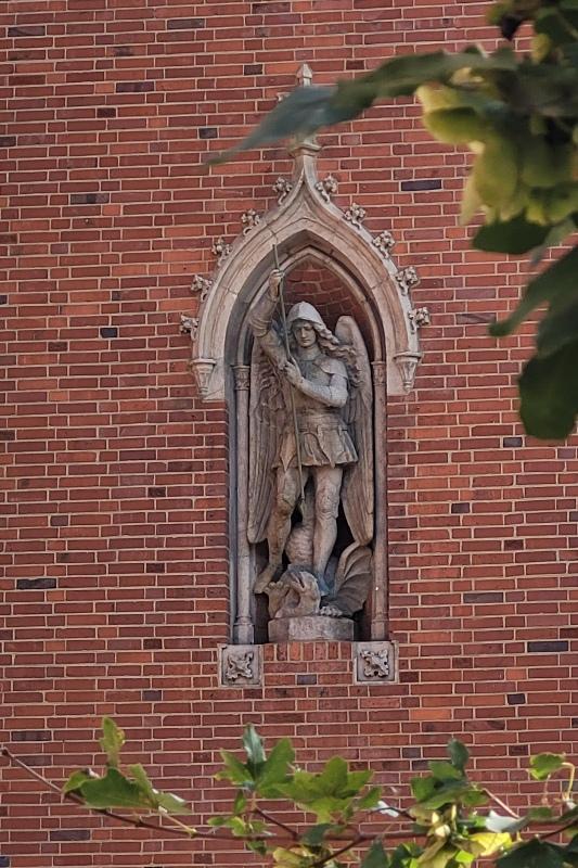 rzeźba Michała Archanioła wmurowana w czerwoną ceglaną ścianę